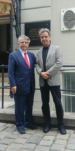 23 Ιουνίου 2018, στην «Οδό Ελλήνων», μπροστά στον ιστορικό ορθόδοξο ναό του Αγίου Γεωργίου, που ήταν ναός των Οθωμανών υπηκόων, όπως ο Ρήγας και οι συμμάρτυρες Σύντροφοί του, ο πρόεδρος της Επιστημονικής Εταιρείας Φερών-Βελεστίνου-Ρήγα και κύριος ομιλητής στις τιμητικές εκδηλώσεις, Δρ. Δημ. Καραμπερόπουλος με τον κ. Ορέστη Δαγκωνάκη, μέλος του οργανωτικού φορέα των εκδηλώσεων του «Κοινωνικοπολιτιστικού Συλλόγου της ελληνικής Κοινότητας Βιέννης «Ρήγας Φεραίος». Διακρίνεται πίσω η τιμητική πλάκα με την ανάγλυφη μορφή του Ρήγα που εντοιχίστηκε το 1998, κατά τις εκδηλώσεις της επετείου των διακοσίων χρόνων από τον μαρτυρικό θάνατό του.